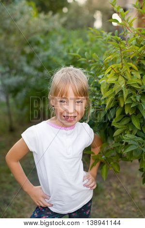 Portrait of the girl in the green bushes, close-up