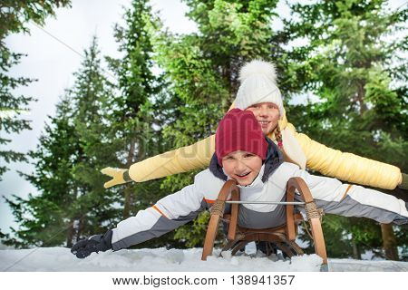Picture of two friends boy and girl sledging belly-whop at winter wood