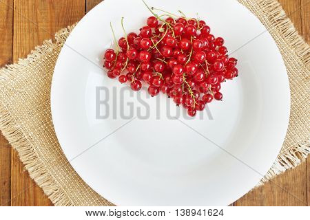 Berries of a red currant on the white plate on the brown wooden texture