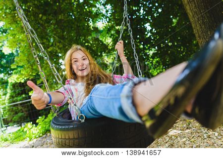 Little girl on a playground. Child playing outdoors in summer. Kids play on school yard. Happy kid in kindergarten or preschool. Children having fun at daycare play ground. Toddler on a swing.