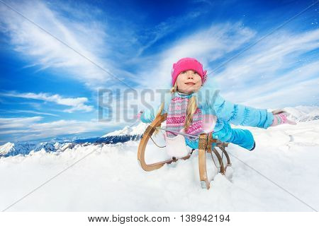 Little girl in blue coat and pink hat on sledge and stretched hands in the mountain