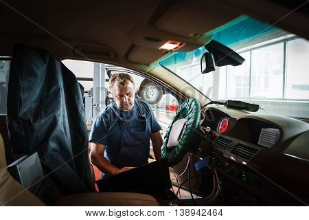Professional serviceman checking car with laptop. Repair shop worker making diagnostics for car on-board computer. Electronic block of automobile checking