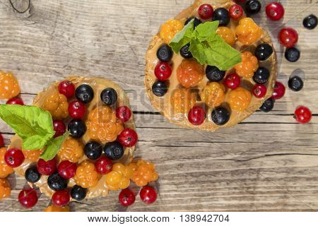 toast of white bread with peanut butter and berries cloudberries, blueberries and red currants