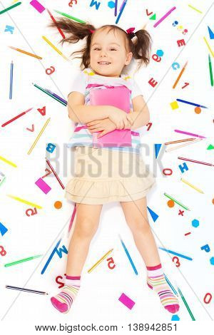 Top view of cute girl holding pink book, laying among school office supplies