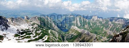 Mountain world in Switzerland, view from Säntis on the Alpstein-Massif with the Lake Seealp in Appenzellerland,  steep rocks and snow fields, panoramic
