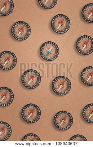 Overhead shot of arranged compasses on brown paper background