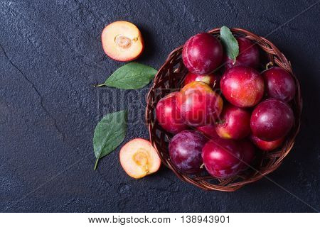 plums in basket on a dark stone background .