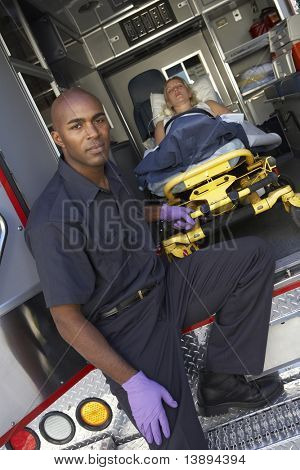 Male paramedic preparing to unload patient from ambulance