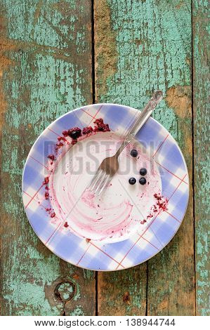 Empty plate with blueberry pie remains on turquoise background overhead view