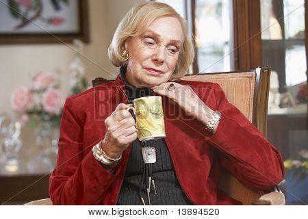 Senior woman drinking hot beverage