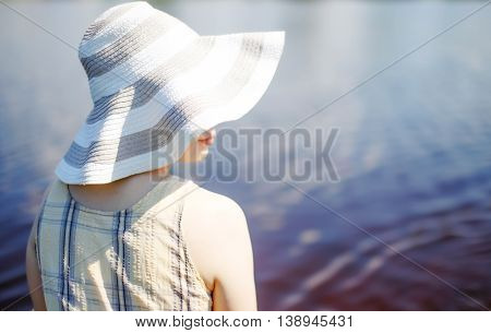 girl in hat sitting near the water. woman in a wide-brimmed hat in profile. the concept of summer vacation. empty space for your text