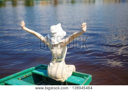 happy young woman enjoying sunny morning on the river. girl stretching with pleasure sitting on a wooden boat in the water. view from the back