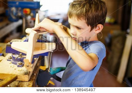 boy making model airplane made of wood. child doing crafts of wood in the workshop