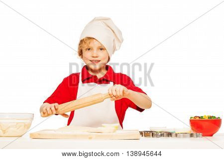 Young baker, kid boy in apron and toque, making dough with rolling pin, isolated on white