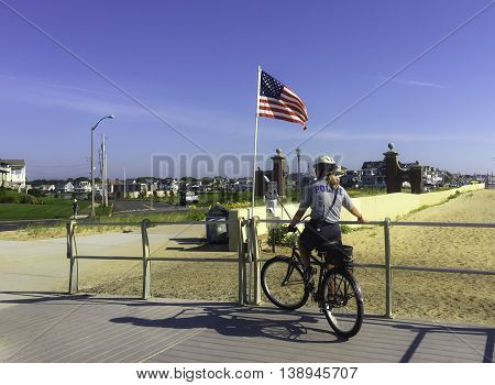 Spring Lake NJ USA July 18 2016 Policewoman on bicycle patrolling the boardwalk near an American flag.