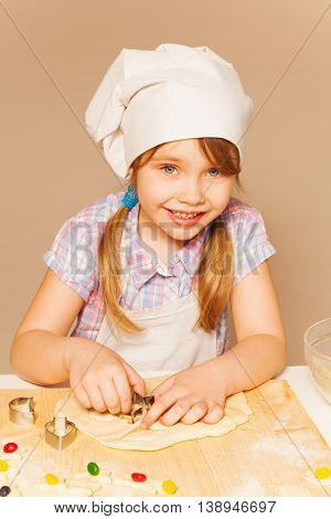 Cute young baker, girl in white apron and toque, cutting off the dough for candy filled cookies