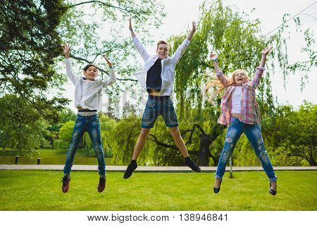 Smiling kids having fun and jumping at grass. Children playing outdoors in summer. teenagers communicate outdoor.