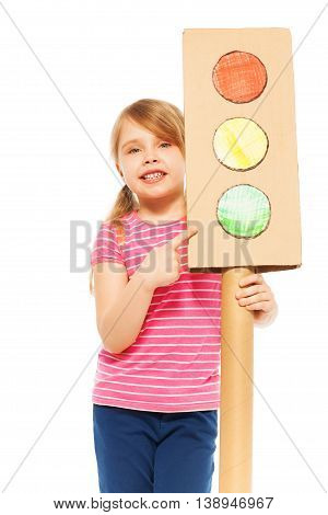 Close-up picture of smiling girl, pointing to the green light of handmade cardboard light-signal, isolated on white