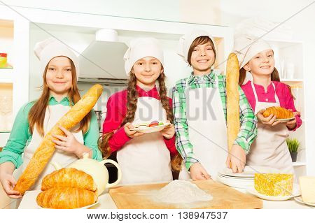 Four young cooks, boy and girls standing in row with croissants, macaroons and baguettes at the kitchen