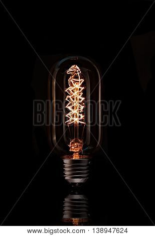 Tall glowing light bulb with angular filament