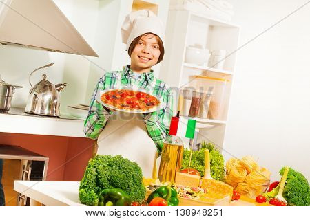 Young boy in white apron and cook's hat demonstrates meal of traditional Italian cuisine in the kitchen
