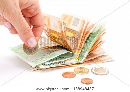 Money euro coins and banknotes. Hand putting money to save up, isolated on white