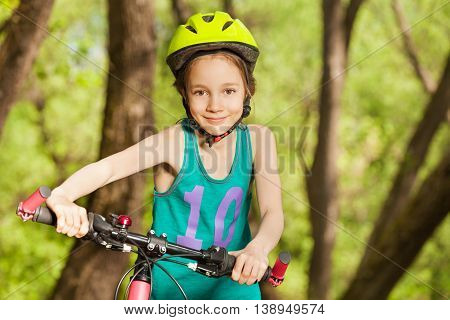 Portrait of beautiful sporty girl in bicycle helmet, driving her mountain bike by handlebar