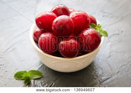 Delicious red plums in a wooden bowl selective focus.