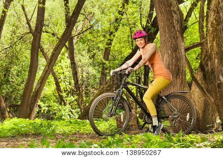 Side view of sporty woman in bright sportswear and helmet, riding the bike in spring sunny wood
