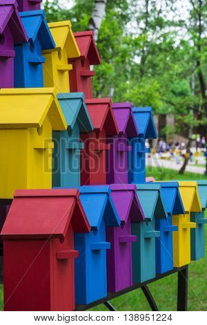 Rows of colorful birdhouses in the park. The new multicolored nesting boxes. Photo with limited depth of field.