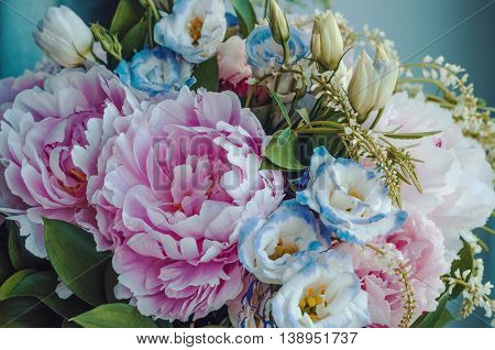 Beauty bunch of pink peonies peony and blue eustoma roses flowers, green leaf on background. Spring or summer lovely bouquet. Bloom love concept. Card, text place, copy space. Wallpaper, trendy color