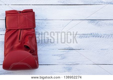 One red boxing glove on a white wooden background