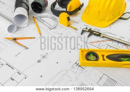 Construction plans with yellow helmet and drawing tools on blueprints