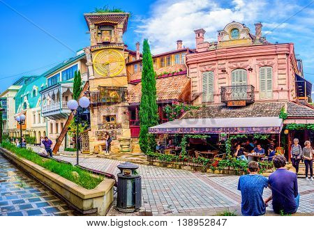 TBILISI GEORGIA - MAY 28 2016: The leaning clock tower of Rezo Gabriadze Puppet Theatre with the art cafe from the right on May 28 in Tbilisi.