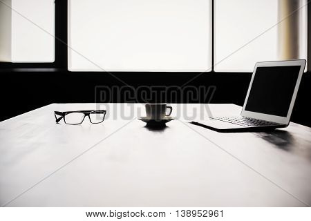 Backlit office desktop with blank laptop screen coffee cup and glasses. Mock up