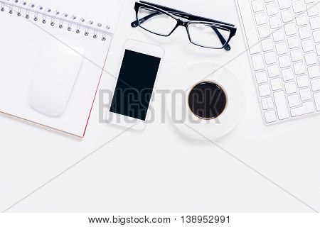 Top view of office desktop with blank mobile phone glasses coffee cup computer mouse keyboard and spiral notepad. Closeup Mock up