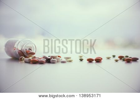 Different pills falling out of prescription bottle on blurry background