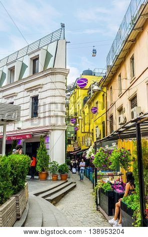 TBILISI GEORGIA - MAY 28 2016: The narrow streets of old town hides cozy cafes wine houses and other unique places offering Georgian cuisine and local wine on May 28 in Tbilisi.