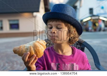 Cute little boy with blue hat sitting at the table looking at tasty croissant he is eating.