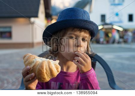 Cute little boy with blue hat sitting at the table stuffing croissant into his mouth.