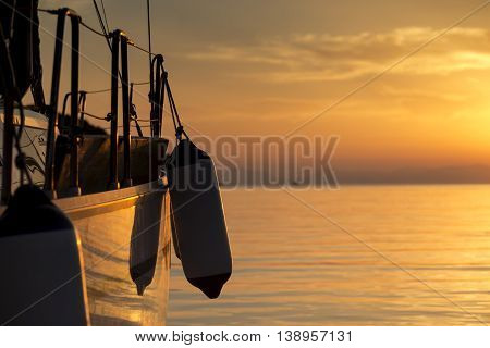 Detail of a boat anchored in the pear with buoys hanging from it on a sunset in Syvota bay