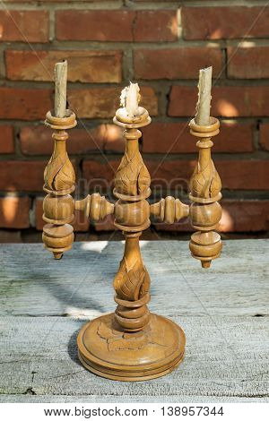 Vintage wooden candlestick on a wood old table near brick wall