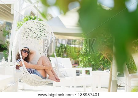 Young woman sitting in a woven rattan hanging basket with cushions enjoying the morning sun in an outdoor cafe by the sea