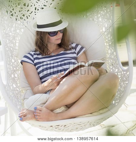 Young woman sitting in a woven rattan hanging basket with cushions enjoying the morning sun in an outdoor cafe by the sea reading a book