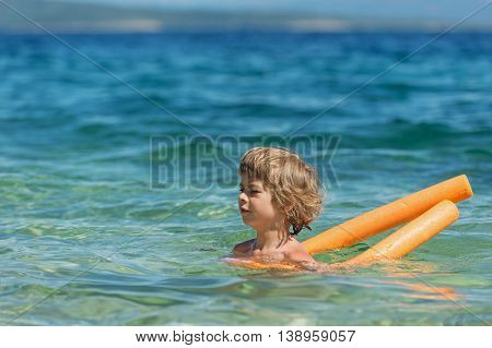 Little boy learning to swim with cell foam water noodle water log or woggle