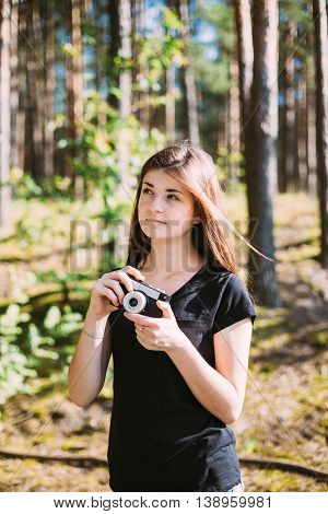 Happy Red-haired Caucasian Girl Young Woman Photographer Taking Pictures The Old Retro Vintage Film Camera In Summer Green Forest. Girl Dressed In A Black T-shirt. Girl Looking Up