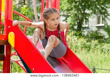 Little sportive girl playing on playground, sitting on the slide