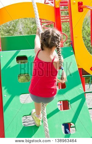 Little girl dressed in a red jersey playing on playground, climbing the wall on a rope with her back