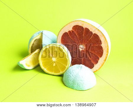 Creative concept photo of grapefruit and lemons covered with mint paint on green background.
