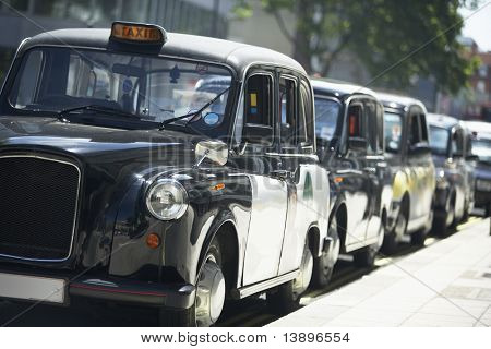 London Taxis Lined Up On Sidewalk